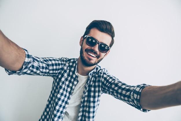 L'heure des selfies ! photo de studio de beau jeune homme à lunettes de soleil faisant selfie et souriant
