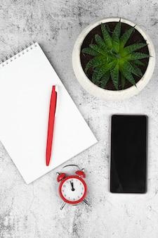 Heure tardive sur l'horloge. téléphone intelligent, réveil rouge et ordinateur portable sur un espace en bois. concept de date limite.