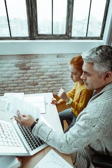 Heures d'ouverture. vue de dessus d'un bel homme mûr assis avec sa fille tout en travaillant