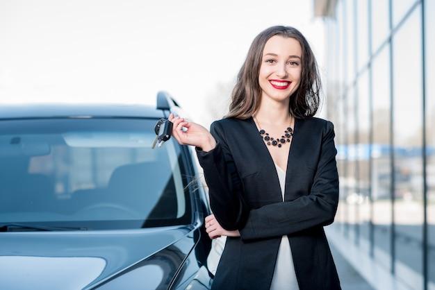 Heureuse acheteuse tenant des clés près de la voiture devant le bâtiment moderne d'avtosalon