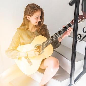 Heureuse adolescente assise sur l'escalier en jouant de la guitare