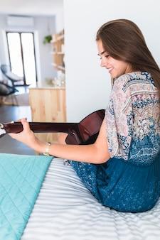 Heureuse adolescente assise sur le lit en jouant de la guitare