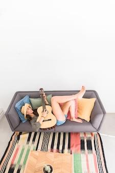 Heureuse adolescente couchée sur le canapé en jouant de la guitare