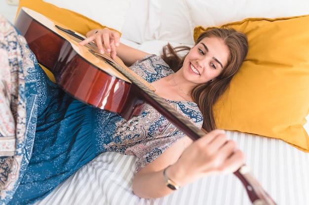 Heureuse adolescente couchée sur le lit en jouant de la guitare