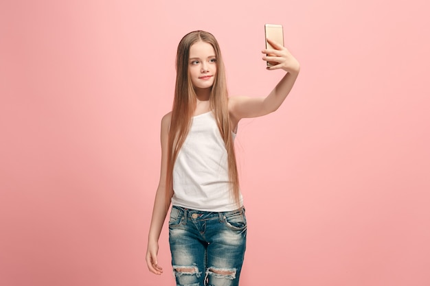Heureuse adolescente debout, souriant sur le mur rose, faisant selfie photo par téléphone mobile. émotions humaines, concept d'expression faciale. vue de face.