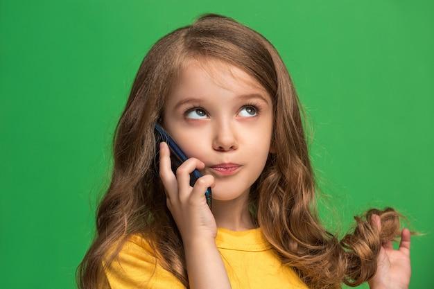 Heureuse adolescente debout, souriant avec un téléphone mobile sur vert branché. beau portrait de femme demi-longueur