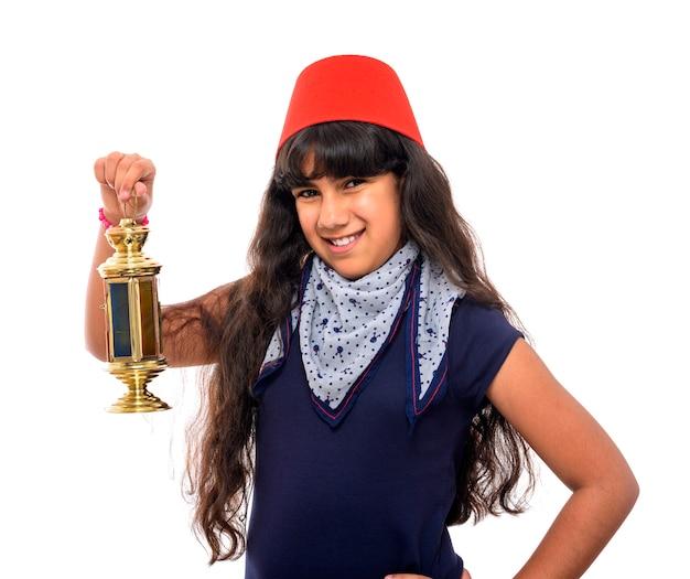 Heureuse adolescente avec fès tenant la lanterne du ramadan
