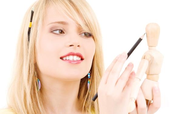 Heureuse adolescente avec mannequin modèle en bois sur blanc