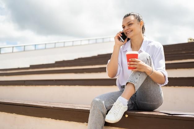 Heureuse adolescente parlant au téléphone tenant une tasse de papier café profitant d'une journée ensoleillée assis dans l'amphithéâtre.