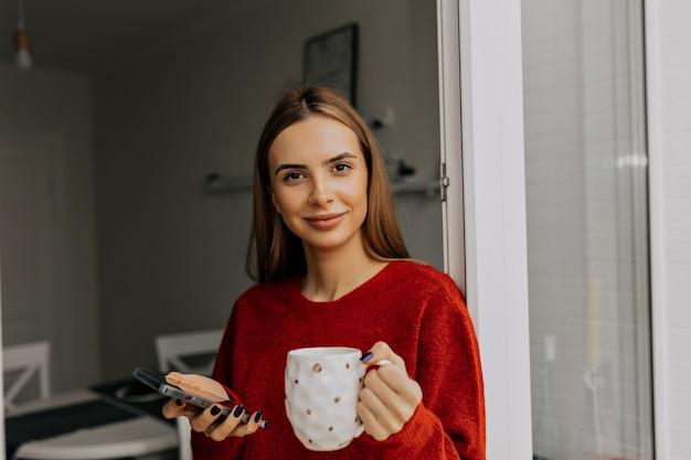 Heureuse adorable dame aux cheveux brun clair, boire du café à la maison par temps chaud