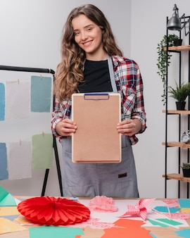 Heureuse artiste féminine séduisante montrant le presse-papiers avec du papier brun ordinaire