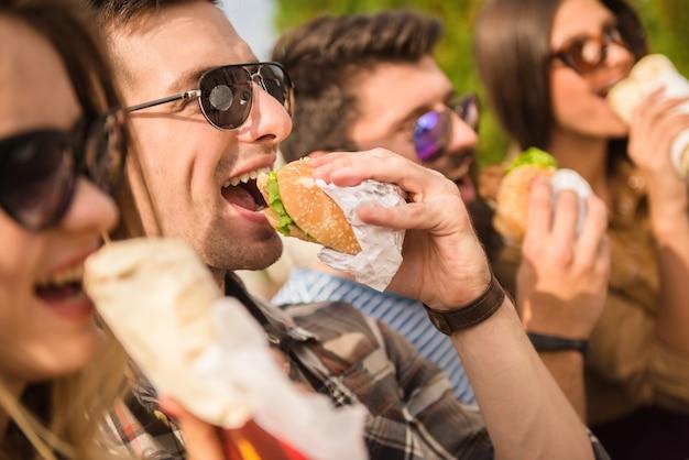 Heureuse assise dans le parc et manger du fast-food avec des amis.