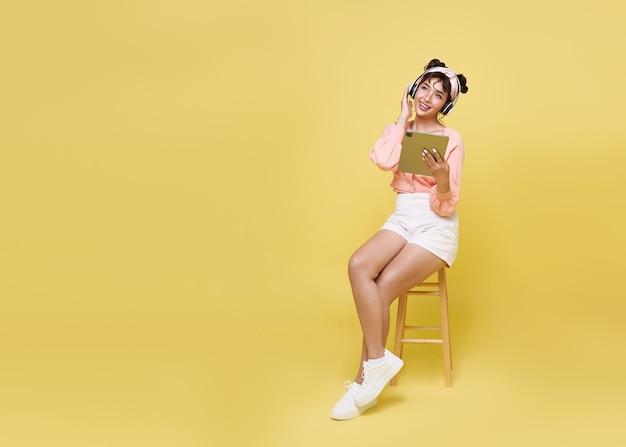 Heureuse belle adolescente asiatique assise sur une chaise et tenant une tablette à la main avec des écouteurs sans fil, écoutant de la musique sur fond d'espace de copie jaune.