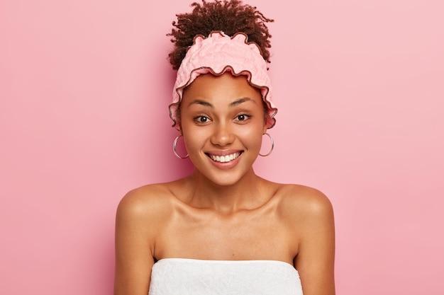 Heureuse belle afro lady sourit agréablement, enveloppée dans une serviette, porte un couvre-chef de bain doux, aime prendre un bain, isolé sur un mur rose