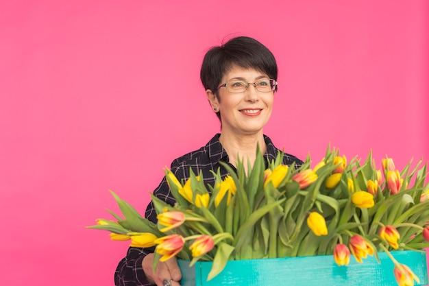 Heureuse belle brune caucasienne femme d'âge moyen avec grande boîte de tulipes sur fond rose.