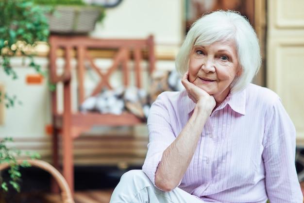 Heureuse belle dame âgée regardant la caméra à l'extérieur