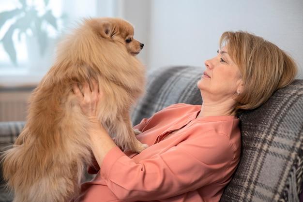 Heureuse belle dame positive, femme âgée âgée assise au canapé dans le salon à la maison avec elle