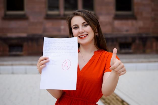 Heureuse belle étudiante en robe rouge montrant du papier avec un bon résultat de test
