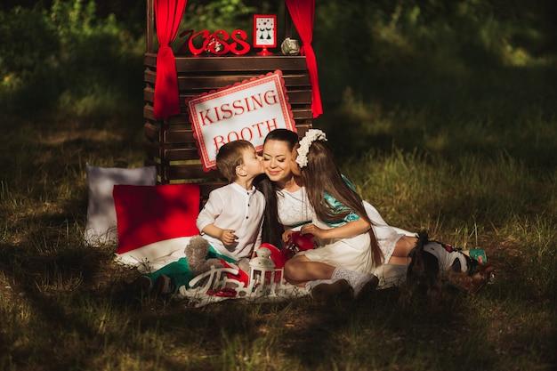 Heureuse et belle famille dans la nature séance photo mère et enfants se détendre sur un pique-nique