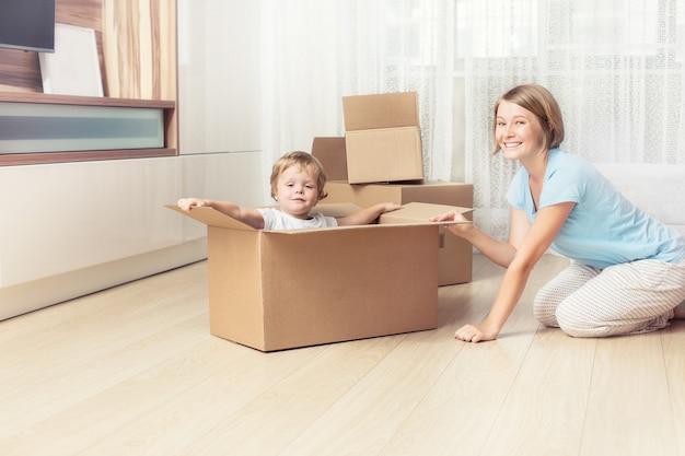 Heureuse et belle famille mère et enfant ensemble dans une nouvelle maison avec des boîtes en carton