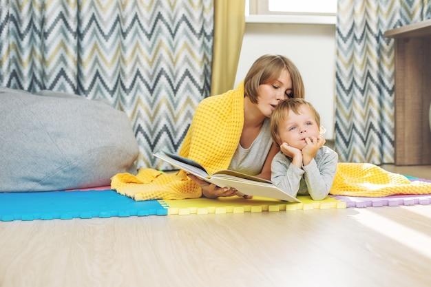 Heureuse et belle famille mère et enfant lisant ensemble un livre couché dans la pépinière