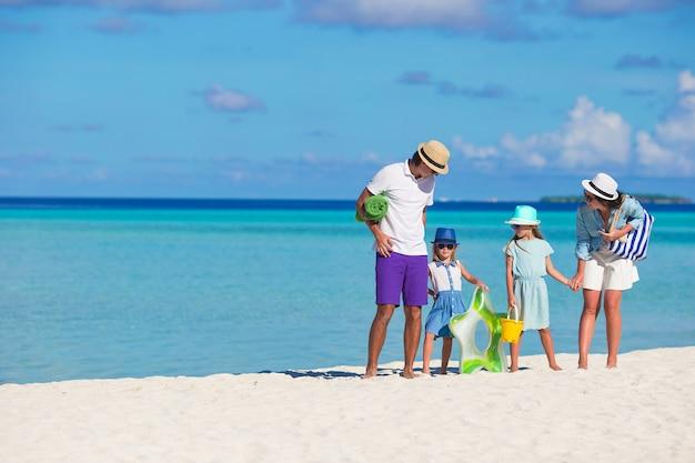 Heureuse belle famille sur la plage blanche pendant les vacances d'été