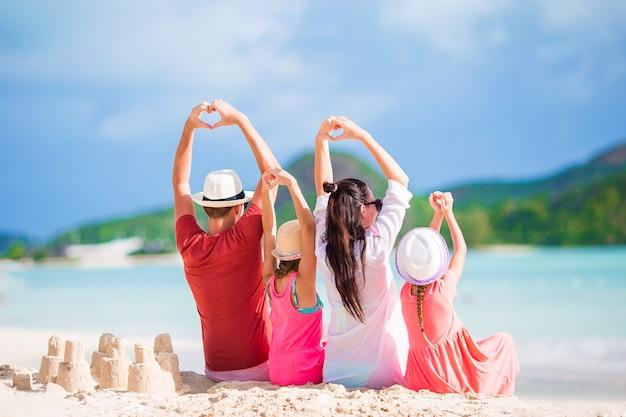 Heureuse belle famille sur la plage blanche s'amuser