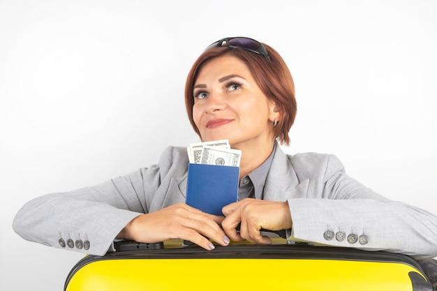 Heureuse belle femme d'affaires avec passeport et bagages partant en voyage. vacances et divertissements. recherchez des endroits où voyager.