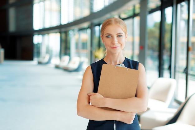 Heureuse belle femme d'affaires avec le presse-papier au bureau.