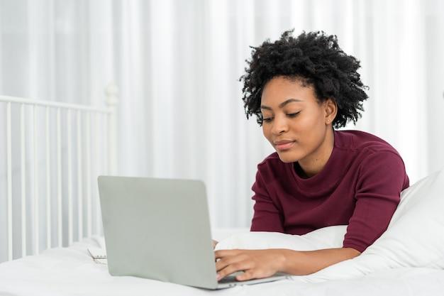 Heureuse belle femme afro-américaine décontractée travaillant sur un ordinateur portable tout en étant assise sur le lit dans la maison.
