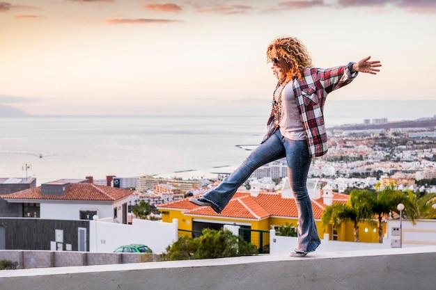 Heureuse belle femme d'âge moyen marchant en équilibre s'amusant comme des enfants avec vue sur la ville