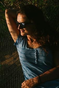 Heureuse belle femme allongée dans un hamac près de l'océan.