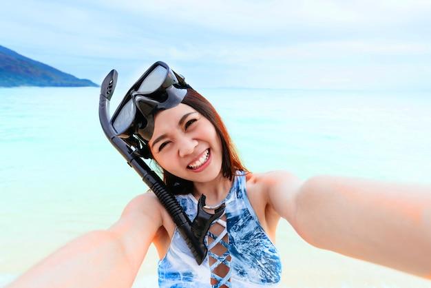Heureuse belle femme asiatique avec masque de plongée en apnée prenant selfie sur la plage près de la mer