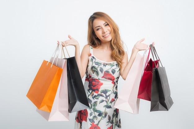 Heureuse belle femme asiatique portant des sacs à provisions sur gris isolé