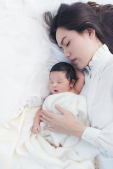 Heureuse belle femme asiatique regardant son bébé endormi