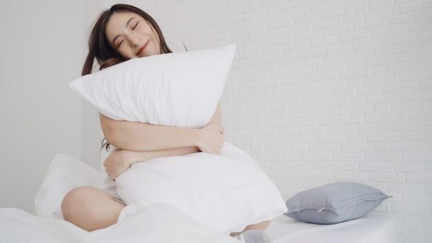 Heureuse belle femme asiatique se réveiller en souriant et en étirant ses bras dans son lit dans la chambre.