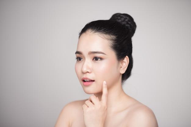 Heureuse belle femme asiatique souriante touchant son visage.