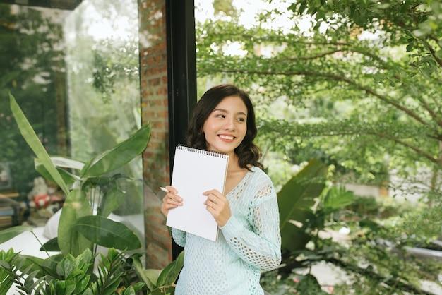 Heureuse belle femme asiatique tenant un livre ou un journal sur fond extérieur naturel vert.
