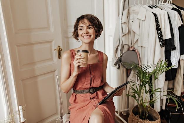 Heureuse belle femme aux cheveux courts en robe élégante en lin boit du café et regarde ailleurs