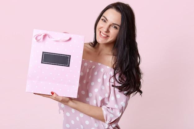 Heureuse belle femme aux cheveux noirs, vêtue d'une robe à pois, détient un sac cadeau avec un cadeau, a une expression faciale positive