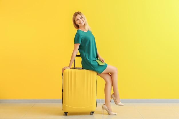 Heureuse belle femme avec bagages et passeport près du mur de couleur