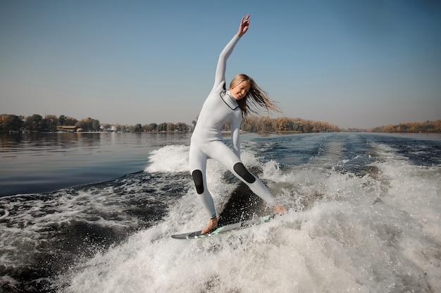 Heureuse belle femme blonde en maillot de bain blanc à cheval sur le wakeboard vert sur les genoux pliés