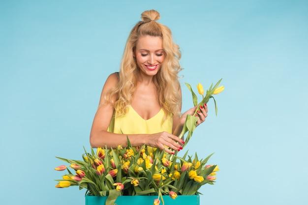 Heureuse belle femme caucasienne blonde avec une grande boîte de tulipes sur fond bleu.