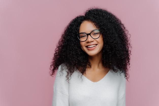 Heureuse belle femme avec une coiffure frisée, sourit doucement à la caméra, porte des lunettes optiques et un pull décontracté blanc