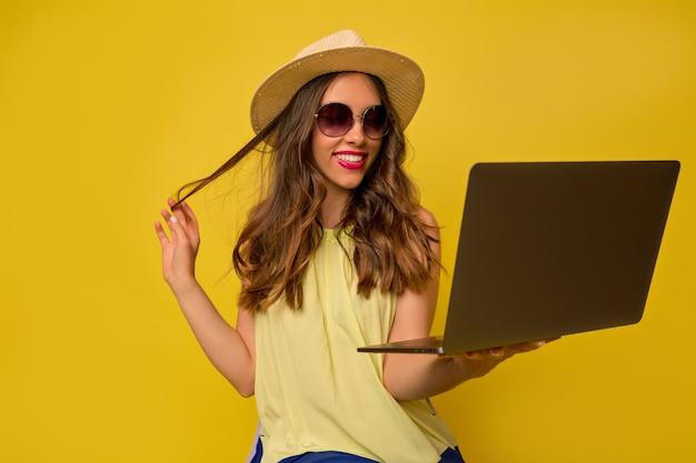 Heureuse belle femme européenne portant chapeau et lunettes d'été travaillant avec un ordinateur portable