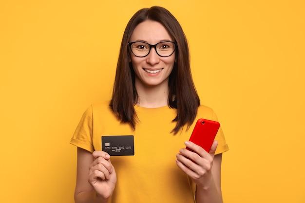 Heureuse belle femme à lunettes et t-shirt jaune à l'aide de smartphone et carte de crédit pour les achats en ligne dans la boutique en ligne