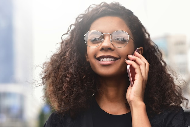 Heureuse belle femme marchant et écrivant ou lisant des messages sms