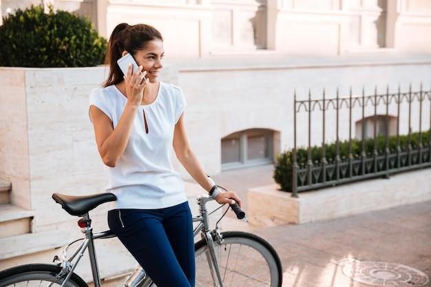 Heureuse belle femme parlant au téléphone s'appuyant sur un vélo dans la rue