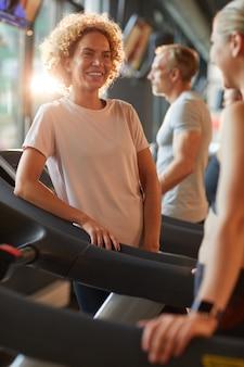 Heureuse belle femme parlant à son amie pendant leur entraînement sportif en salle de sport