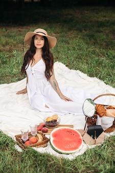 Heureuse belle femme portant un chapeau à bords et une robe blanche en position debout et tenant un panier de pain dans le parc d'été